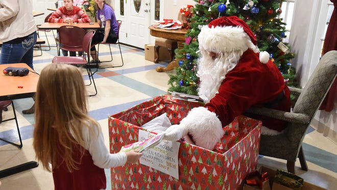 A small group of children opened presents from Santa Claus on Wednesday, Dec. 23, 2015 at the Serenity shelter in Mountain Home. The families who come in for the Christmas gathering are current clients staying at the local domestic violence shelter or outreach clients — those who have transitioned out of the shelter.