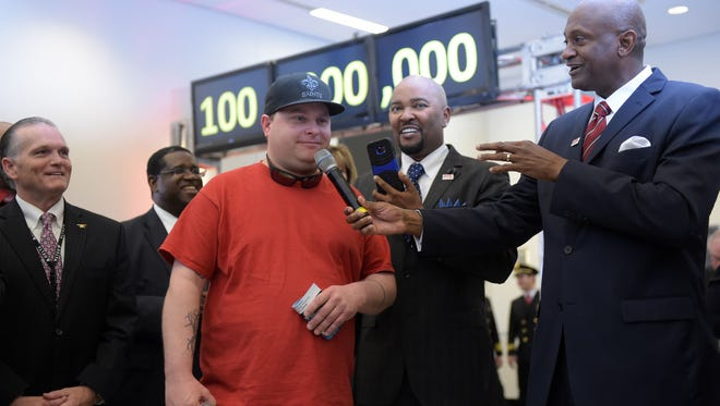 Passenger Larry Kendrick, middle, speaks next to Hartsfield-Jackson Atlanta International Airport Manager Miguel Southwell (right) at a ceremony naming Kendrick the airport's 100 millionth passenger on Dec. 27, 2015.