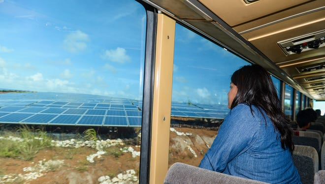 GPA has signed contracts with solar power companies to meet a requirement for renewable energy. In this photo, Doris Ann Hocog peers out from a bus window on a tour of the NRG Renew solar farm in Dandan in December 2015.