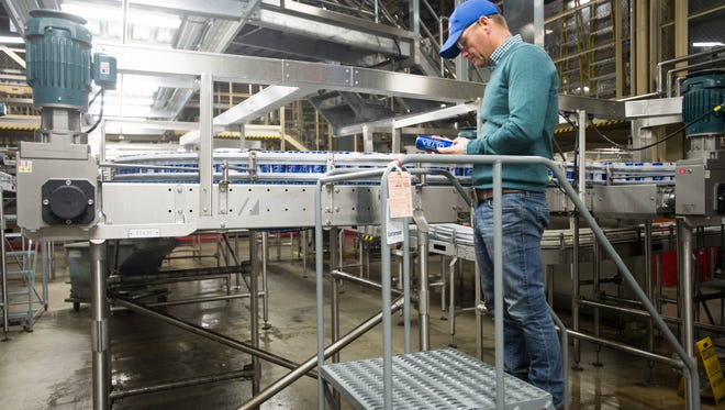 Gene Bocis, Anheuser-Busch's Fort Collins brewery general manager, inspects product on the canning line last month. The St. Louis brewing company received tax credits from the state to add a fourth canning line and 41 full-time manufacturing jobs to its Northern Colorado location.