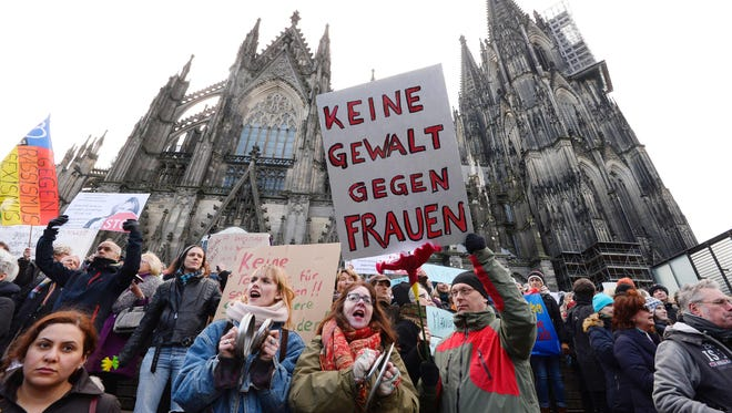 """A man holds up a sign reading """"No violence against women"""" as he takes part in a demonstration in front of the cathedral in Cologne, western Germany."""