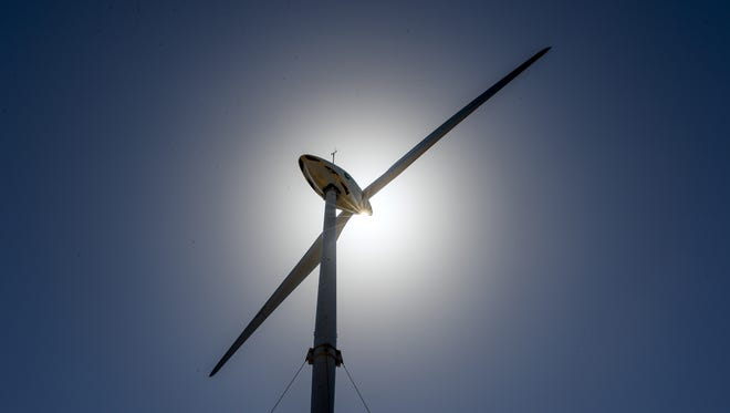 A wind turbine, able to produce approximately 275 kilowatts of power, towers high above the treeline along Route 17 in Windward Hills on Tuesday, Jan. 12.