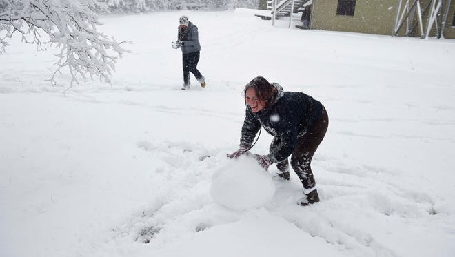 Autumn Maize, 19, makes a huge snowball and Amy Putnam make a snowball Friday morning and the area gets covered in snow Jan. 22, 2016 in Nashville, Tenn.