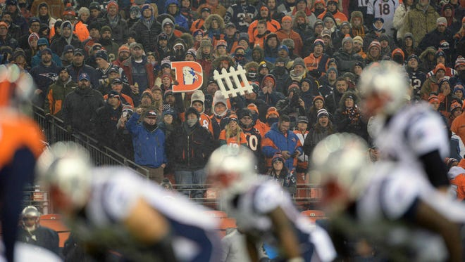 Denver Broncos fans hold a defense sign as the New England Patriots line up for a play in the first quarter at Sports Authority Field at Mile High on Nov 29, 2015. The two teams will meet again Sunday in the AFC Championship.