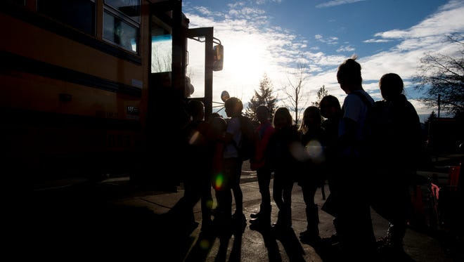 Students board a school bus to head home after a day at Tavelli Elementary School on Tuesday in Fort Collins. A new computer app allows parents of Poudre School District students to track their children's buses.