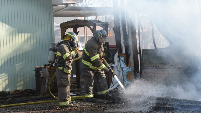 Northeast Lakeside volunteer firefighters work the scene of a structure fire at 147 Pine Cone Drive in Mountain Home Thursday afternoon.