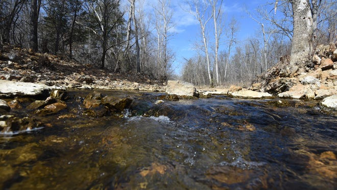 Water flows through Hicks Creek as it passes the Mountain Home Water Treatment Plant Monday. The Arkansas Department of Environmental Quality labeled the creek as impaired due to pathogens and nitrate in the water.