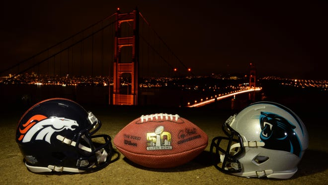 General view of NFL Wilson Duke football with the Denver Broncos and Carolina Panthers helmets overlooking the Golden Gate bridge and downtown San Francisco skyline in advance of Super Bowl 50.