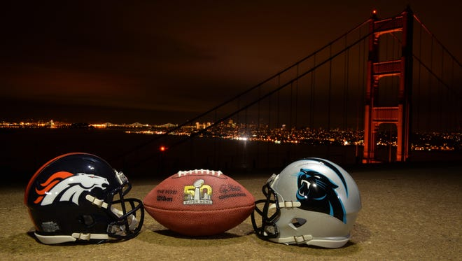 An NFL football and the Denver Broncos and Carolina Panthers helmets overlook the Golden Gate bridge and downtown San Francisco skyline in advance of Super Bowl 50.