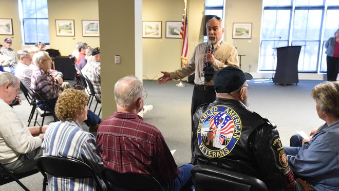 Richard Bowyer, standing, a contract liaison, talks Friday, Feb. 19, 2016 to veterans during a town hall meeting at Arkansas State University Mountain Home. Several hundred veterans attended the meeting and heard Bowyer say there was nothing unusual about the way the contract was let out, a contention the current local providers disagree with.