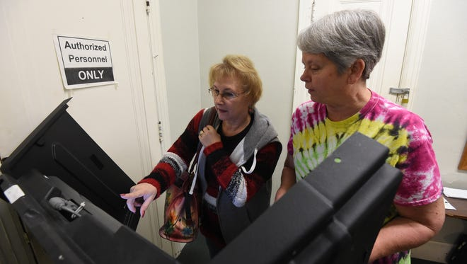 Election worker Amy Stuart, right, helps Yellville voter Rheta Van Cott, left, cast her vote at the Marion County Courthouse in Yellville on Friday. As of Friday morning, more than 1,200 Marion County residents had cast their votes ahead of Super Tuesday.