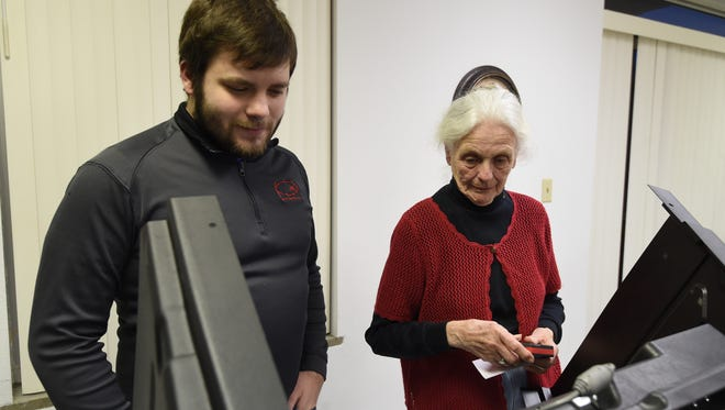 Judy Young, a poll worker in Marion County, preps a machine for Marshall Dillard, who voted in the Democratic primary during Super Tuesday.