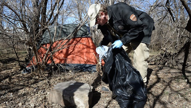 Park Ranger Karl Sanders cleans up an abandoned campsite along the Poudre River at Lee Martinez Park on Monday, March 14, 2016.