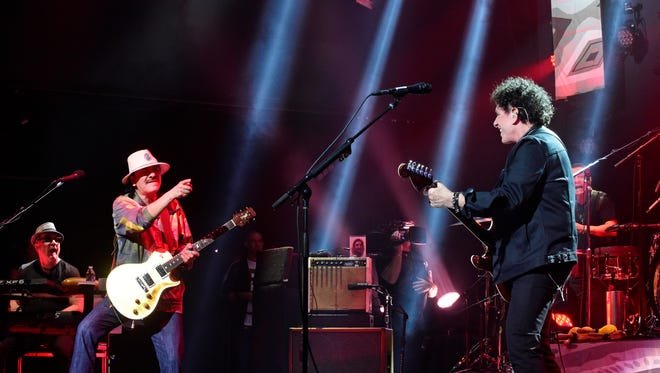 """Carlos Santana points to band member Neal Schon during dress rehearsals Sunday night at """"The House of Blues."""""""