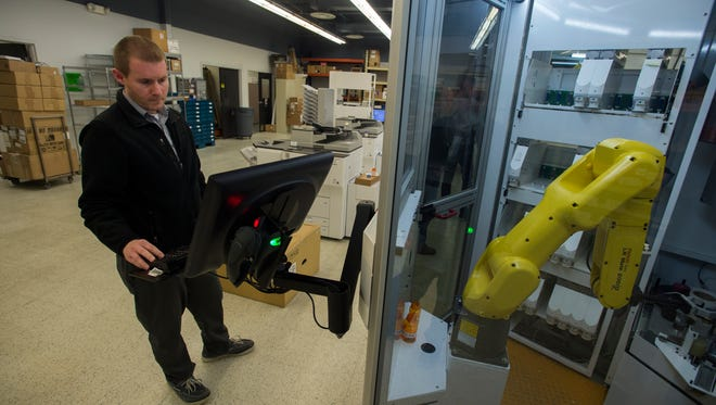 Mike Lewis, software system tester at Innovation, tests a PharmASSIST RDSx machine inside the company's Johnson City facilities on Wednesday.