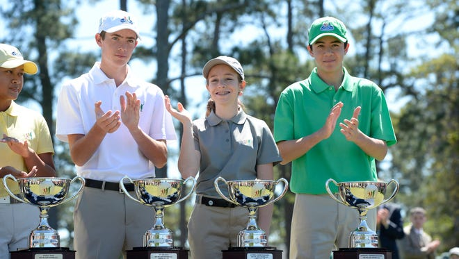 Girls 14-15 winner Alyssa Montgomery from Knoxville, Tenn., waves during the trophy presentation during the 2016 Drive, Chip and Putt Championship at Augusta National GC. At left is Ty Briggs from Manteca, Calif., and Michael Thorbjornsen from Wellesley, Mass., is at right.