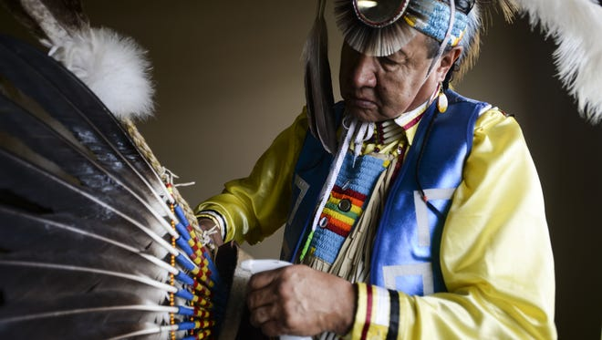 Tommy Lee Ghost Dog cleans his headdress during The Northern Colorado Intertribal Pow-wow Association's annual spring powwow contest and art market Saturday, April 18, 2015 at Northside Aztlan Community Center in Fort Collins, CO.