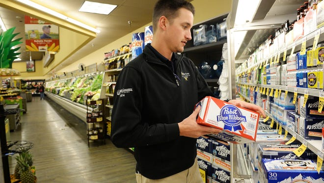 Brett Jones, sales representative with High Country Beverage, stocks 3.2 percent alcohol content beer at Safeway at Drake Road and Taft Hill Road on Wednesday, April 6, 2016.