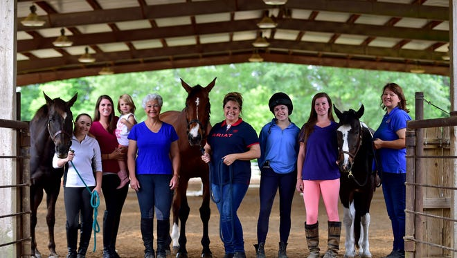 Grace Galtelli, from left, Lauren Strickland, 2-year-old M.C. Strickland, Fontaine Bowie, Michelle Curry, Amber Curry, Kayla Pavlick and Dawn Pavlick stand in an arena at Blue Ribbon Riding Academy in Canton.