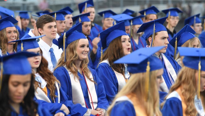 Seniors cheer and laugh as one of their speaks Friday night during the Mountain Home High School graduation ceremony.