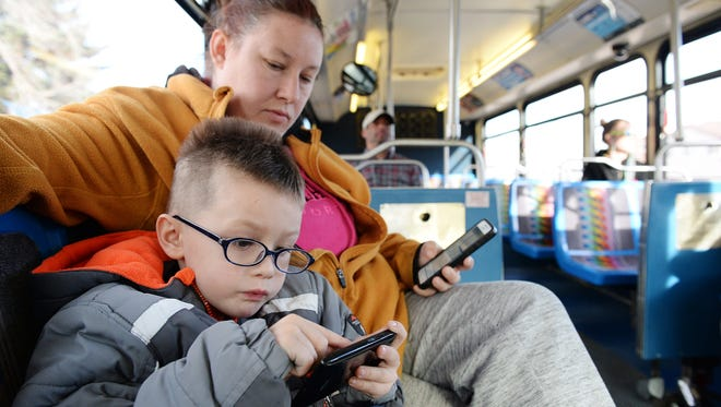 Fawn Martin and her son Zayden Slone, 5, ride the bus to Summitview Church, where they will eat dinner and sleep for the week, on March 15, 2016. Martin said it can be challenging to keep her son entertained on long bus rides.