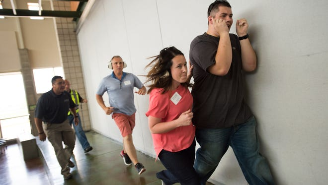 Kaycee Headrick of the Boys and Girls Club assists a student actor into a lockdown area during an active shooter simulation at Kinard Middle School Wednesday, June 1, 2016. Education administrators received training in dealing with dangerous situations in a school environment.