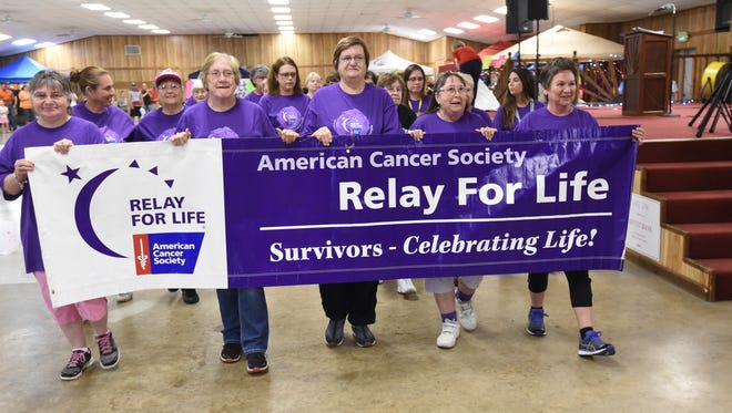 """Participants carry a banner at this year's American Cancer Society Relay For Life in the Educational Building at the Baxter County Fairgrounds. Relay gives people across the globe a chance to """"celebrate the lives of people who have battled cancer, remember loved ones lost and fight back against the disease,"""" the American Cancer Society states. Visit baxterbulletin.com for a photo gallery."""