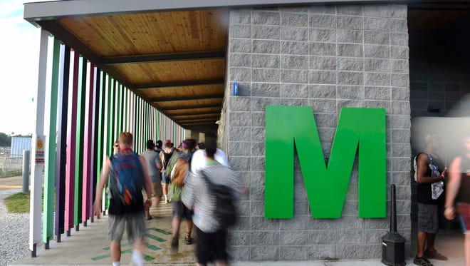 Men enter the new bathroom the first day at Bonnaroo Music and Arts Festival June 9, 2016 in Manchester, Tenn.