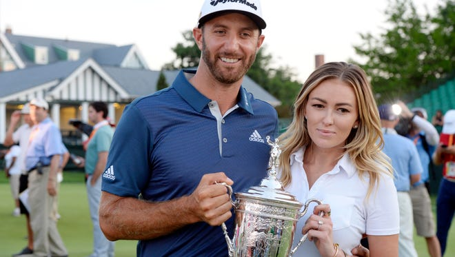 Dustin Johnson and fiance Paulina Gretzky hold the championship trophy after the U.S. Open golf tournament at Oakmont Country Club.