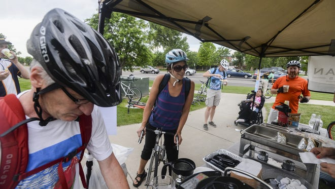 Cyclists line up for and eat food at a Bike to Work Day station near Timberline and Harmony roads Wednesday, June 24, 2015 in Fort Collins, CO.