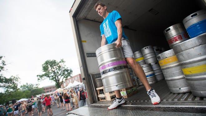 Volunteer Austin Bengford unloads a keg during the Colorado Brewers' Festival in Washington Park Saturday, June 25, 2016.