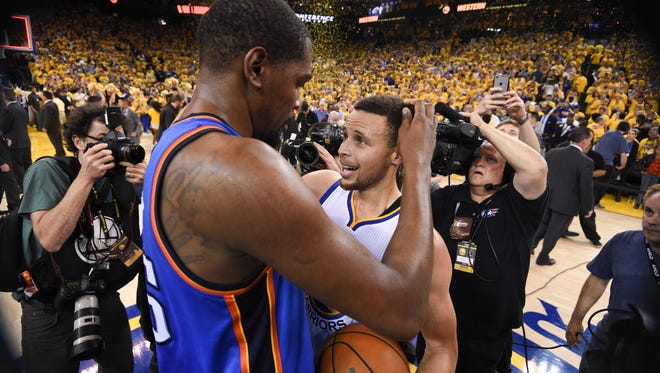 Golden State Warriors guard Stephen Curry (30, right) is congratulated by Oklahoma City Thunder forward Kevin Durant (35) after Game 7 of the Western conference finals. Durant has decided if he can't beat the Warriors, to join them.