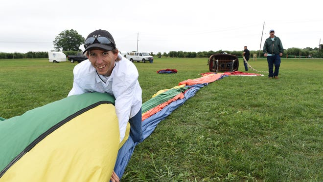 Balloon Rides Over Orlando crew chief, Clayton Helberg, gathers up a balloon after an unsuccessful attempt at inflating it Saturday afternoon during the Dutchess County Regional Chamber of Commerce's Hudson Valley Hot-Air Balloon Festival at Barton Orchards in Poughquag.