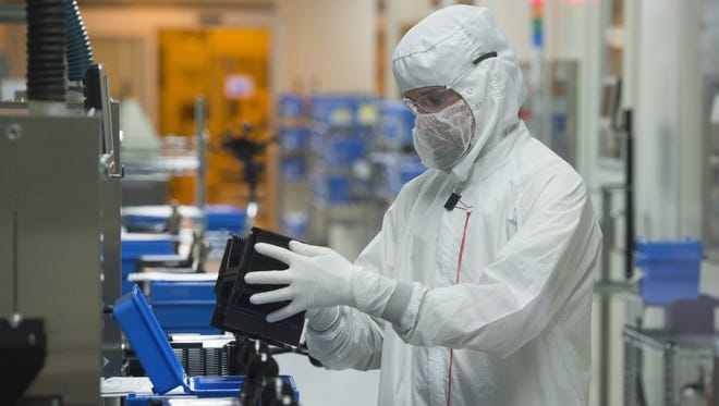 A man works in one of the manufacturing labs at Avago Technologies' Fort Collins facility Friday, December 11, 2015. The company, now known as Broadcom, develops microchips for cell phones.
