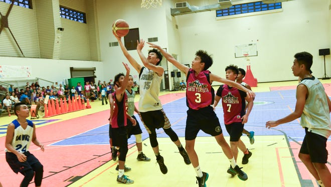 Rench Pingol of the Sharks drives around Ethan Rosario to the basket during the GYBA U16 boys league championship basketball game held on July 25 at the Dededo sports complex.