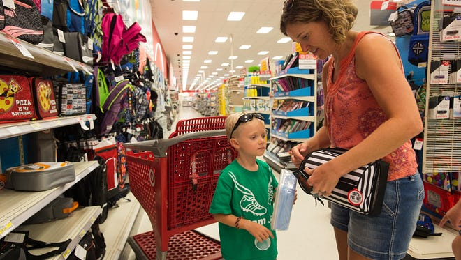Dawn Eger helps her son, Ryan, pick out a lunch box Wednesday at Super Target. Ryan will be a first-grader this year.  Last-minute school supply shoppers are flocking to area retailers before the start of the school year next week.