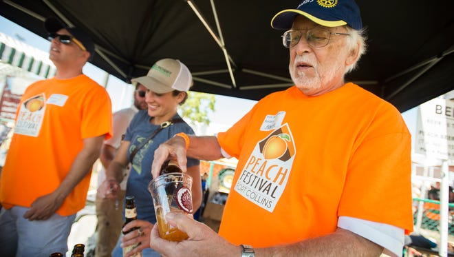 """Mark Korb pours a glass of """"Tree Shaker,"""" a peach IPA from Odell Brewing Company at the Fort Collins Peach Festival at Hughes Stadium Saturday, August 20, 2016. Hosted by the Rotary Clubs of Fort Collins, the event featured activities for kids, live music and plenty of peach inspired foods."""