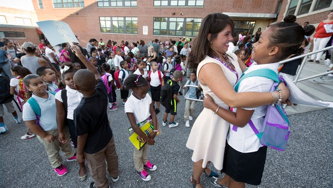 Teacher Marissa James, left, hugs Ja'Tiana Gladfelter before school begins outside Jackson K-8 in York. Ja'Tiana had James for third grade last year,  and this year she'll have James for fourth grade English and social studies.