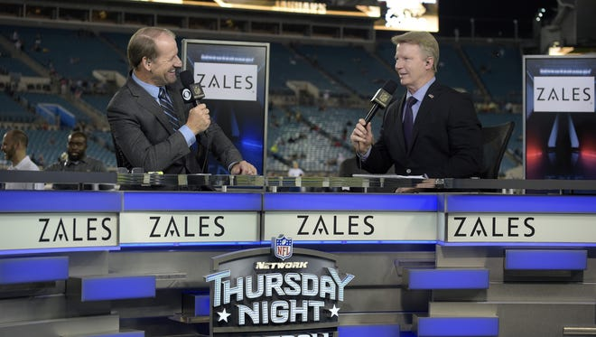Sportscasters Bill Cowher, left, and Phil Simms broadcast from the set on the field before an NFL football game.