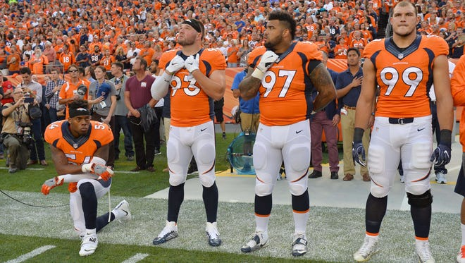 Denver Broncos inside linebacker Brandon Marshall (54) kneels during the national anthem next to defensive end Jared Crick (93) and defensive tackle Billy Winn (97) and defensive tackle Adam Gotsis (99) before the game against the Carolina Panthers at Sports Authority Field at Mile High.