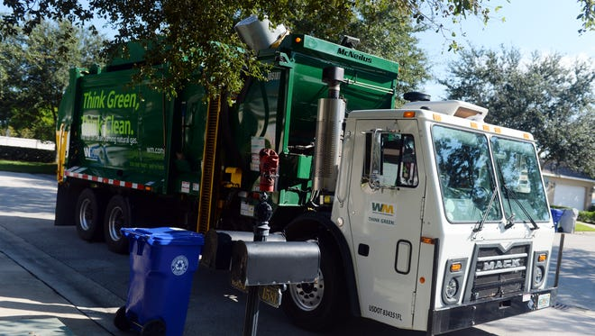 A Waste Management truck driven by Demetrius Houston makes its way Wednesday, Sept. 28, 2016,  through the Pointe West neighborhood in Vero Beach. Each trash cart is embedded with a chip that is scanned as it is loaded into the truck and records the time and day the cart was serviced.
