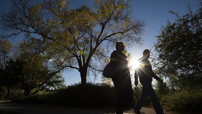 A couple walks past an ash tree along Sheldon Lake in City Park Tuesday, October 4, 2016. The Emerald Ash Borer, a beetle, is expected to arrive in the Fort Collins area in the future and would kill all untreated ash trees.