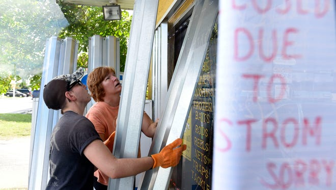 Tanner (left) and Debbie Hrobak, of Port St. Lucie, install storm shutters ahead of Hurricane Matthew on Wednesday, Oct. 5, 2016 at Billy Bones Bait-N-Tackle South in Stuart.