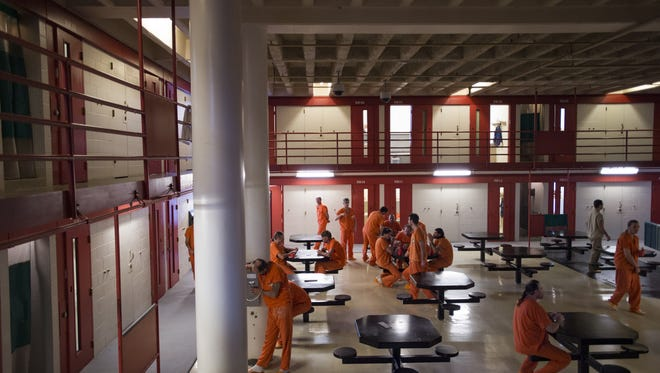Inmates move around a housing area at Larimer County Jail Friday, September 30, 2016.
