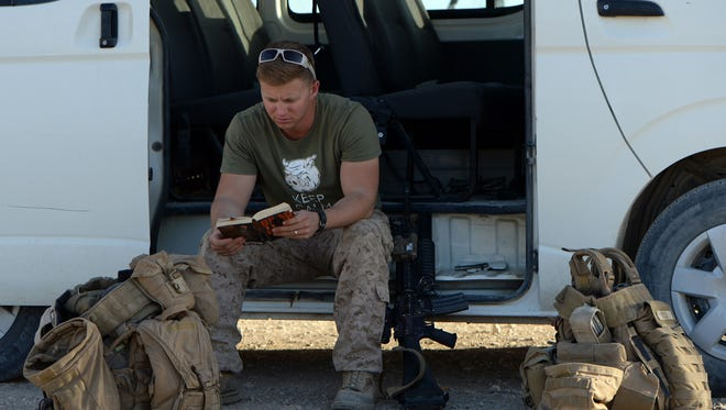 A US Marine reads a book while he waits near transport as British and US troops withdraw from the Camp Bastion-Leatherneck complex at Lashkar Gah in Helmand province on October 26, 2014.