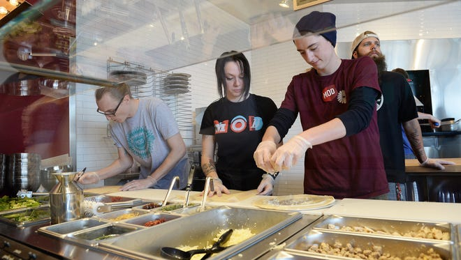 Employees Cody Barnes, from left, Meagan Curry and Colin Darrah prepare orders at Mod Pizza on Monday, October 24, 2016.