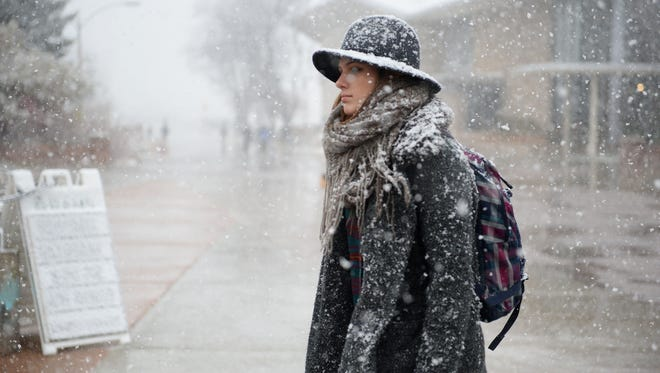 A student walks on the CSU campus during the first seasonal snow on Thursday, November 17, 2016.