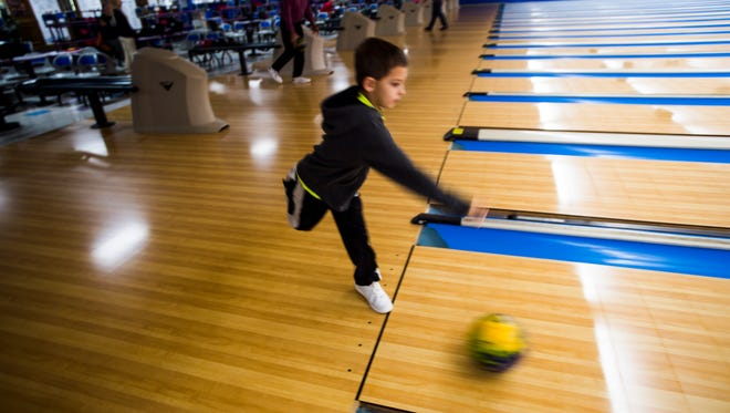 """Thomas Davis, 9, of New Oxford bowls on Sunday with his twin brother, Patrick, and grandfather Rick Davis at Hanover Bowling Center. The Hanover Bowling Center will be offering a """"Quarter Mania"""" special lanes and shoe rentals for 25 cents on Black Friday."""