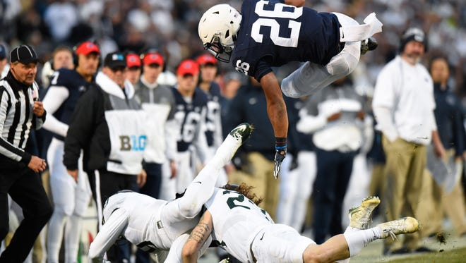 Penn State Nittany Lions running back Saquon Barkley (26) leaps over Michigan State Spartans safety Montae Nicholson (9) and linebacker Chris Frey (23) during the second quarter at Beaver Stadium.