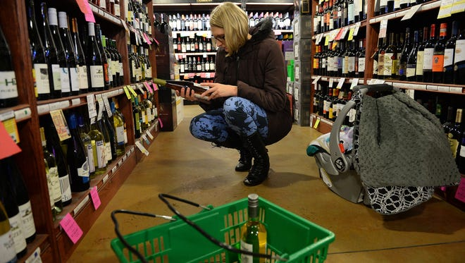 Stephanie Speetzen shops for Christmas presents at Bullfrog Wine & Spirits on Thursday, December 8, 2016. The store is expanding and adding a drive thru.